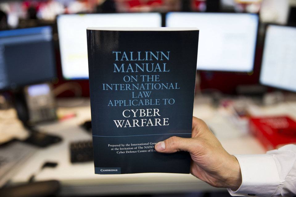 A copy of the Tallinn Manual, a rulebook on cyberwarfare, is held up in a posed photograph in London, Tuesday, March 19, 2013. Even cyberwar has rules, and one group of experts is publishing a manual to prove it. The handbook due to be published later this week applies the venerable practice of international law to the world of electronic warfare in an effort to show how hospitals, civilians, and neutral nations can be protected in an information age fight. (AP Photo/Matt Dunham)