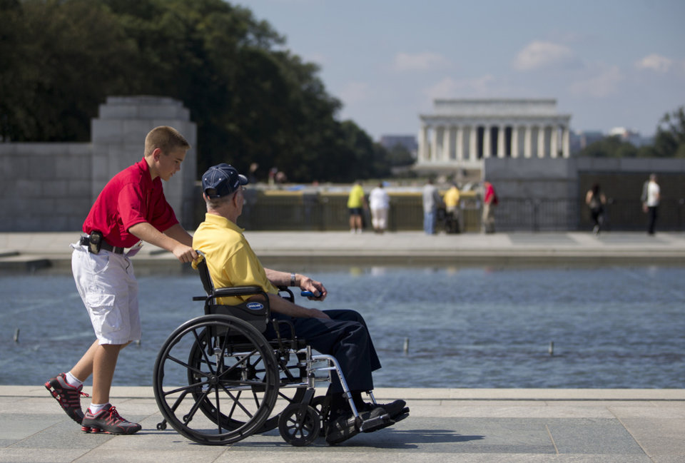 Photo - Korean War veteran Robert Olson, from Iowa, is pushed in his wheelchair by Zach Twedt, also from Iowa, around the National World War II Memorial in Washington, Tuesday, Oct. 1, 2013. Veterans who had traveled from across the country were allowed to visit the National World War II Memorial after it had been officially closed because of the partial government shutdown. After their visit, the National World War II Memorial was closed again. The Lincoln Memorial is seen in the distance. (AP Photo/Carolyn Kaster)