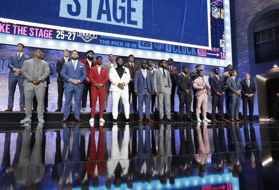 Photo - NFL Commissioner Roger Goodell, right participates in the national anthem with football players ahead of the first round at the NFL football draft, Thursday, April 25, 2019, in Nashville, Tenn. (AP Photo/Mark Humphrey)