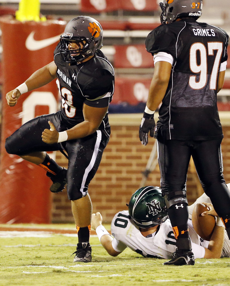 Photo - Norman's High's Cade Parker celebrates his sack of Norman North's quarterback David Cornwell (10) for a loss in the second quarter at Gaylord Family-Oklahoma Memorial Stadium in Norman, Okla., on Thursday, Sept. 5, 2013. Photo by Steve Sisney, The Oklahoman