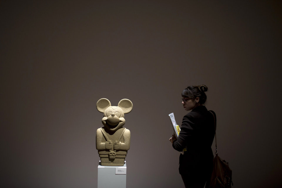 A woman looks at a sculpture by Nadin Ospina titled 'Idol with Skull' on exhibit at the Casa Daros museum in Rio de Janeiro, Brazil, Wednesday, March 20, 2013. Local officials aiming to transform Rio de Janeiro from a sleepy cultural backwater into an art hotspot are inaugurating this week Casa Daros, a new museum that draws on one of the world's premier collections of contemporary Latin American art. Casa Daros, a 12,000-square meter (129,000-square foot) exhibition space housed in a renovated 1866 mansion, will bring to Rio some of the around 1,200 pieces acquired over the past 13 years by independently wealthy Zurich-based collector Ruth Schmidheiny. (AP Photo/Felipe Dana)