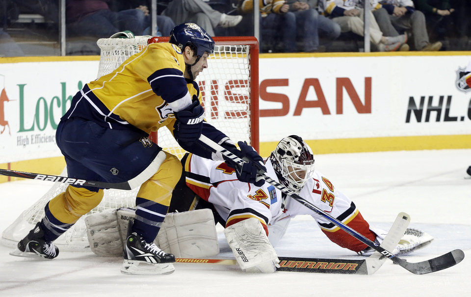 Calgary Flames goalie Miikka Kiprusoff (34), of Finland, blocks a shot by Nashville Predators center David Legwand (11) in the second period of an NHL hockey game, Thursday, March 21, 2013, in Nashville, Tenn. (AP Photo/Mark Humphrey)