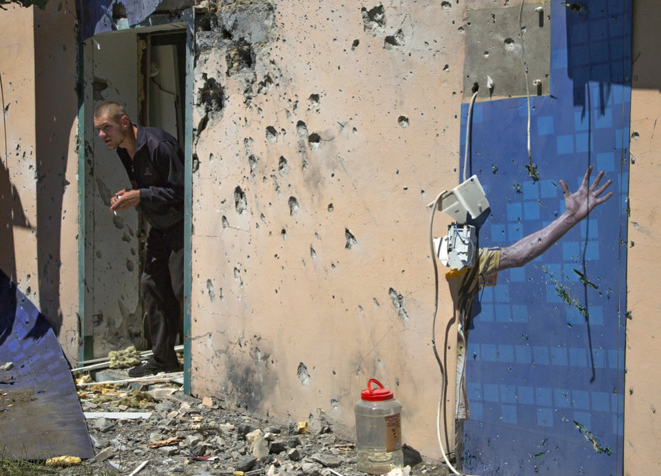 Photo - A man exits from a damaged shop with a destroyed advertisement poster on the right, after shelling in the city of Kramatorsk, Donetsk region, eastern Ukraine, Thursday, July 3, 2014. Residential areas came under shelling on Thursday from government forces. (AP Photo/Dmitry Lovetsky)