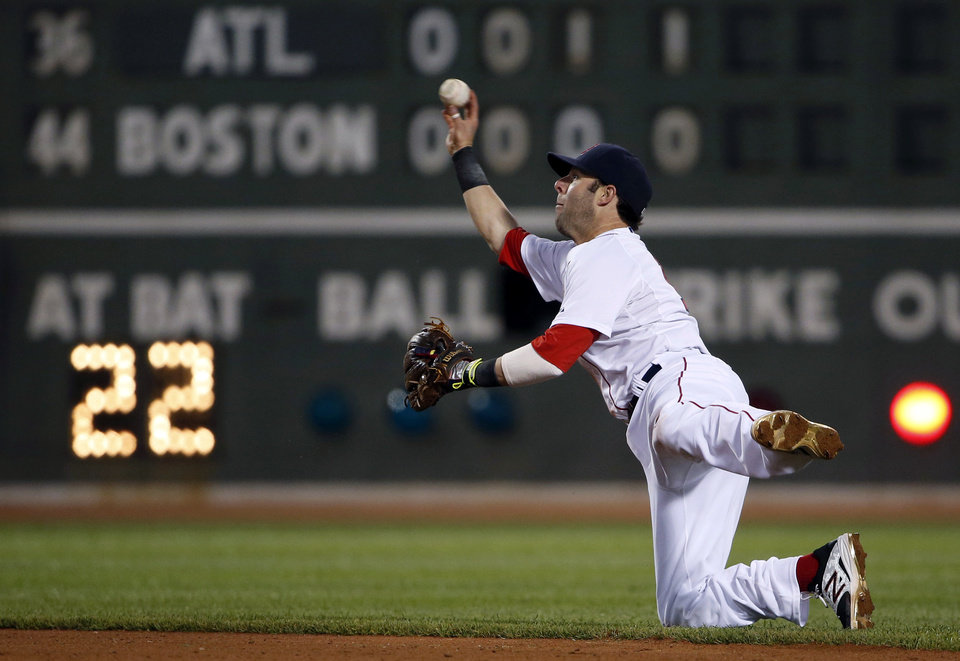 Photo - Boston Red Sox second baseman Dustin Pedroia flips the ball to a teammate after making a diving stop on an infield hit by Atlanta Braves' Jason Heyward during the fifth inning of a baseball game at Fenway Park, Thursday, May 29, 2014, in Boston. (AP Photo/Winslow Townson)