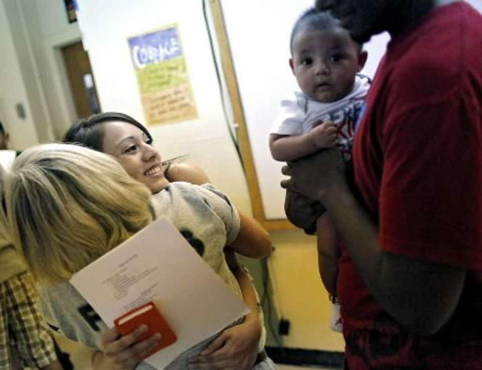 Senior student Naomi Cerda gets a hug from her teacher, Cleda Spaeth (at left) while a classmate, Dimitri Wortham (right) holds Naomi's five-month-old son, Adriel Hernandez, during the Back 2 School Bash at Santa Fe South Charter High School in Oklahoma City on Monday, Aug. 1, 2011. Photo by John Clanton