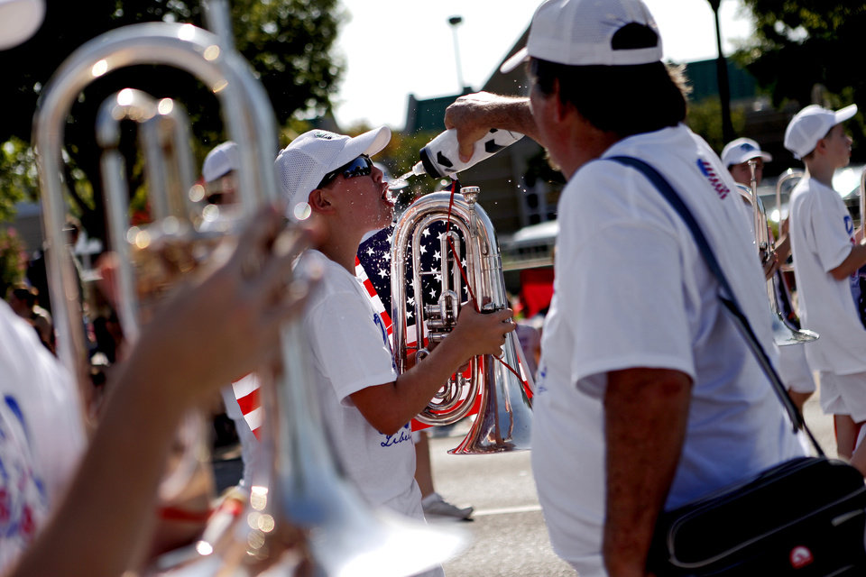 Photo - An Edmond Santa Fe High School band member gets a drink during the LibertyFest Fourth of July Parade in Edmond, Okla., Wednesday, July 4, 2012. Photo by Bryan Terry, The Oklahoman