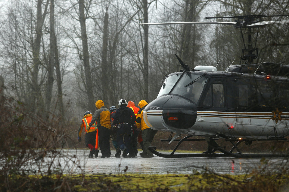 Photo - A helicopter and waiting ground crew transfer a worker injured working on the mudslide into a waiting ambulance from a Snohomish County helicopter near Oso, Wash., Tuesday, March 25, 2014. A massive mudslide struck near Arlington, Wash., on Saturday, killing at least 14 people over the weekend and leaving scores more missing. (AP Photo/The Herald, Mark Mulligan)