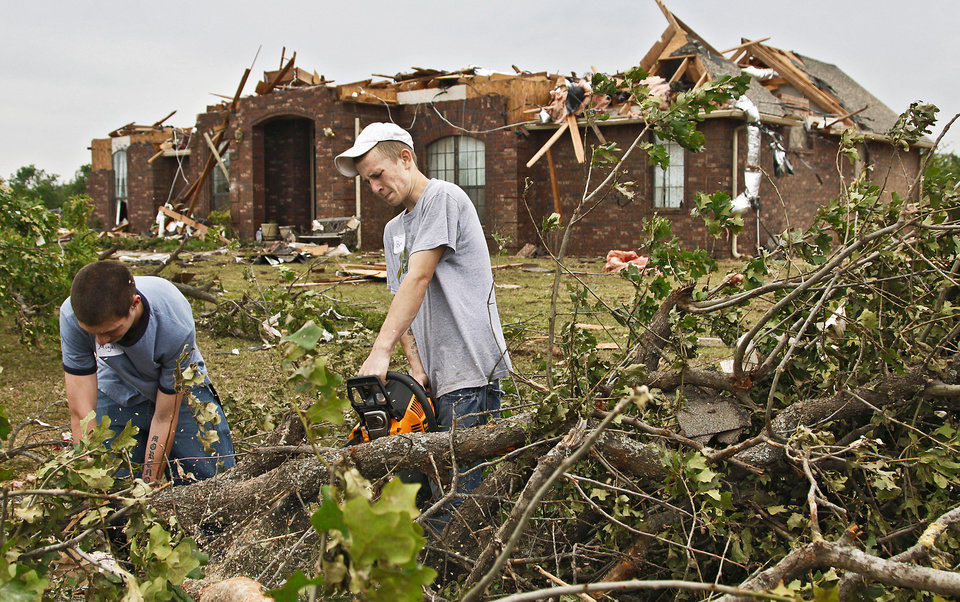 Photo - Little Axe students Miguel Varnell, left, and Ben Dodson  help clean up tornado debris Wednesday. Varnell and Dodson and their friend, Cody Brown, whose school was destroyed by a twister, volunteered their time to help in a neighborhood near SE 59 and Peebly Road. Photo by Chris Landsberger, The Oklahoman
