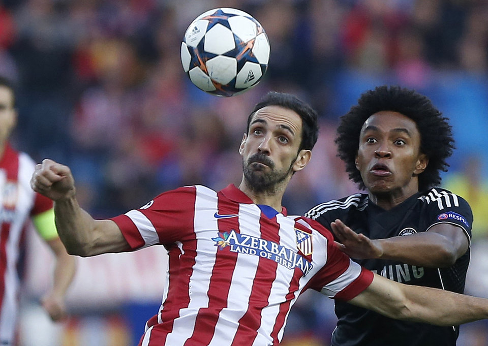 Photo - Atletico's Juanfran, left, clears the ball from Chelsea's Willian during the Champions League semifinal first leg soccer match between Atletico Madrid and Chelsea at the Vicente Calderon stadium in Madrid, Spain, Tuesday, April 22, 2014. (AP Photo/Andres Kudacki)
