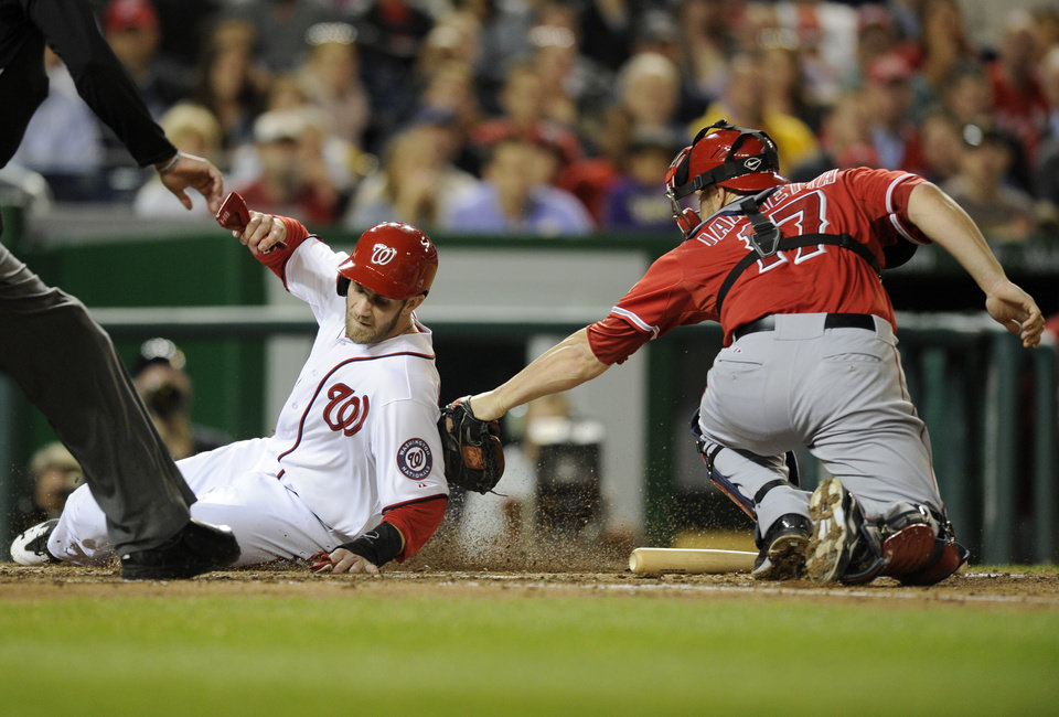 Photo - Washington Nationals' Bryce Harper, left, is  tagged out at home by Los Angeles Angels catcher Chris Iannetta, right, during the fourth inning of a baseball game, Monday, April 21, 2014, in Washington. (AP Photo/Nick Wass)
