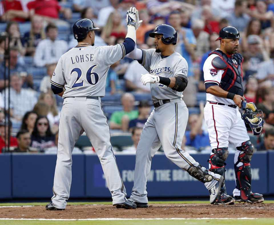 Photo - Milwaukee Brewers center fielder Carlos Gomez  celebrates with pitcher Kyle Lohse (26) as Atlanta Braves catcher Gerald Laird (11) looks on after hitting a two-run home run in the fourth inning of a baseball game Wednesday, May 21, 2014 in Atlanta. (AP Photo/John Bazemore)