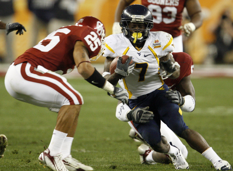 Photo - West Virginia's Noel Devine (7) is brought down by the Oklahoma defense during the first half of the Fiesta Bowl college football game between the University of Oklahoma Sooners (OU) and the West Virginia University Mountaineers (WVU) at The University of Phoenix Stadium on Wednesday, Jan. 2, 2008, in Glendale, Ariz. 