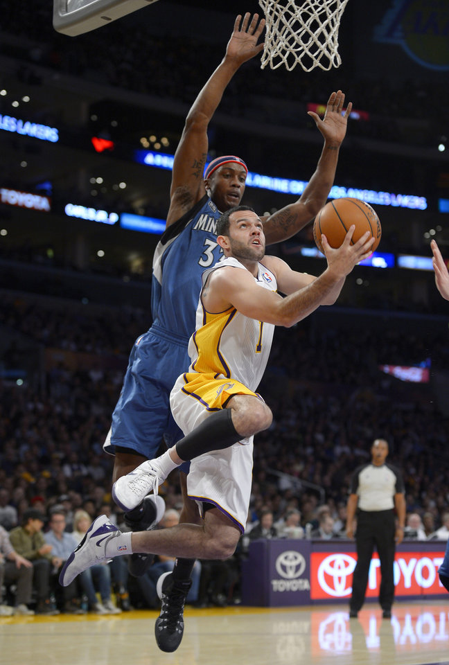 Photo - Los Angeles Lakers guard Jordan Farmar, right, puts up a shot as Minnesota Timberwolves forward Dante Cunningham defends during the first half of an NBA basketball game, Sunday, Nov. 10, 2013, in Los Angeles. (AP Photo/Mark J. Terrill)