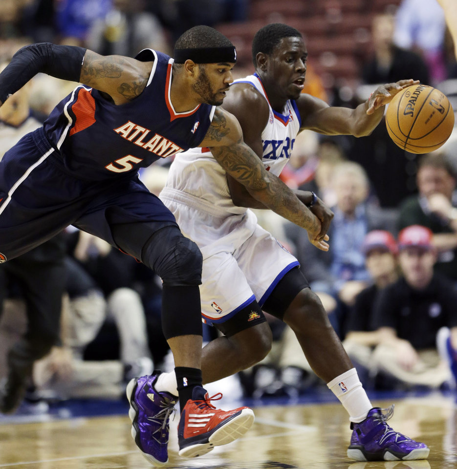 Philadelphia 76ers\' Jrue Holiday, right, and Atlanta Hawks\' Josh Smith chase down a loose ball in the first half of an NBA basketball game, Friday, Dec. 21, 2012, in Philadelphia. (AP Photo/Matt Slocum)