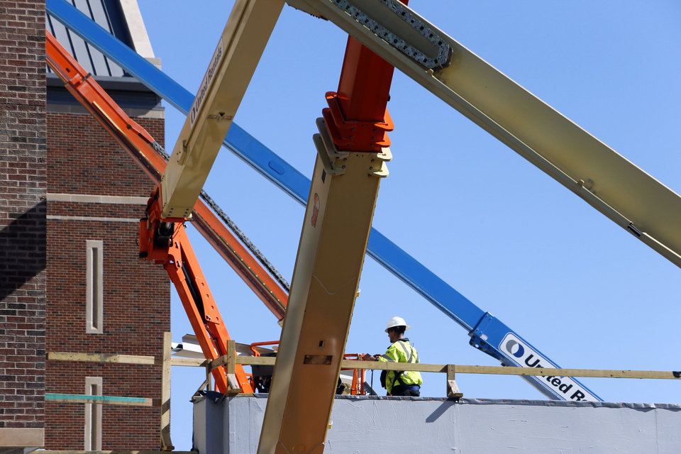 Photo - Right: A crane lifts construction workers to the top of Headington Hall, the University of Oklahoma student residential center being built at Lindsey Street and Jenkins Avenue in Norman.