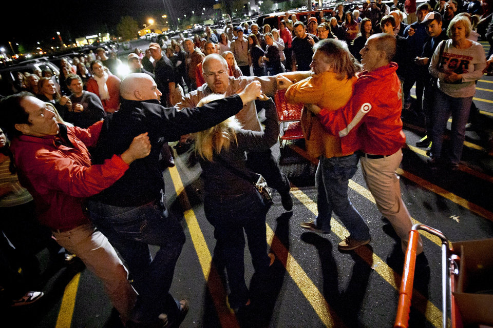Photo -   A crowd gathers as security guards break up a fight between shoppers waiting in line just as the doors open for Black Friday shopping at Target, Thursday, Nov. 22, 2012, in Bowling Green, Ky. Despite a surge of resistance as the sales drew near, with scolding editorials and protests by retail employees and reminders of frantic tramplings past, Black Friday's grip on America may be stronger than ever. (AP Photo/Daily News, Alex Slitz)