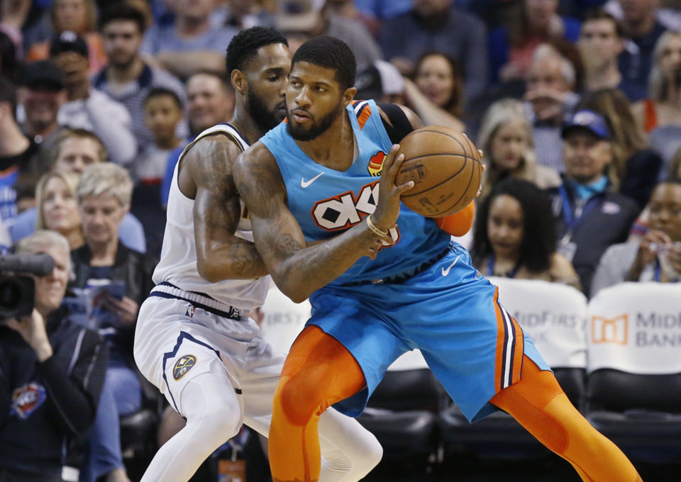 Photo - Oklahoma City Thunder forward Paul George, right, drives against Denver Nuggets guard Will Barton, left, in the first half of an NBA basketball game Friday, March 29, 2019, in Oklahoma City. (AP Photo/Sue Ogrocki)