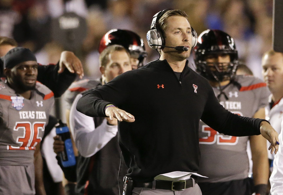 Photo -  Texas Tech coach Kliff Kingsbury sends signals to his team during the first half of the Holiday Bowl NCAA college  football game against Arizona State  Monday, Dec. 30, 2013, in San Diego. (AP Photo/Gregory Bull)