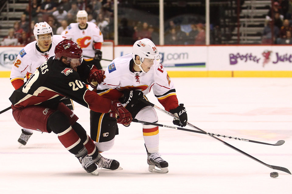 Photo - Phoenix Coyotes defenseman Chris Summers (20) rides Calgary Flames center Jiri Hudler (24) off the puck as Jarome Iginla (12) watches in the first period of an NHL hockey game, Monday, Feb. 18, 2013, in Glendale, Ariz. (AP Photo/Paul Connors)