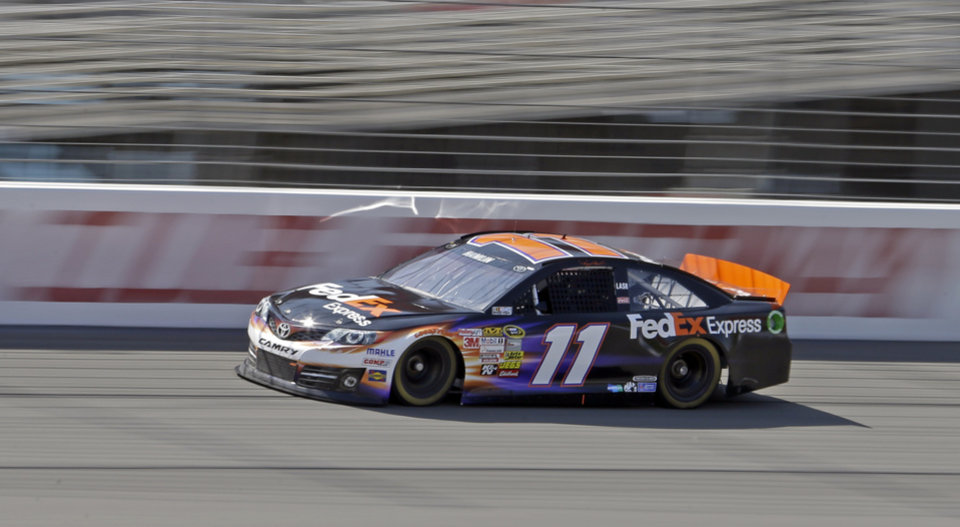 Photo - Denny Hamlin takes his FedEx Express Toyota through practice laps on his way to taking the pole position in later qualifying for the NASCAR Sprint Cup series Auto Club 400 auto race in Fontana, Calif., Friday, March 22, 2013. (AP Photo/Reed Saxon)