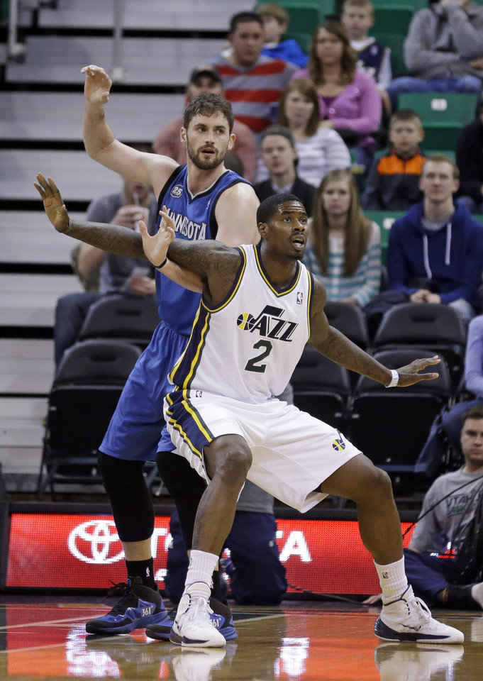 Photo - Utah Jazz's Marvin Williams (2) guards Minnesota Timberwolves' Kevin Love, left, in the first quarter of an NBA basketball game, Saturday, Feb. 22, 2014, in Salt Lake City. (AP Photo/Rick Bowmer)