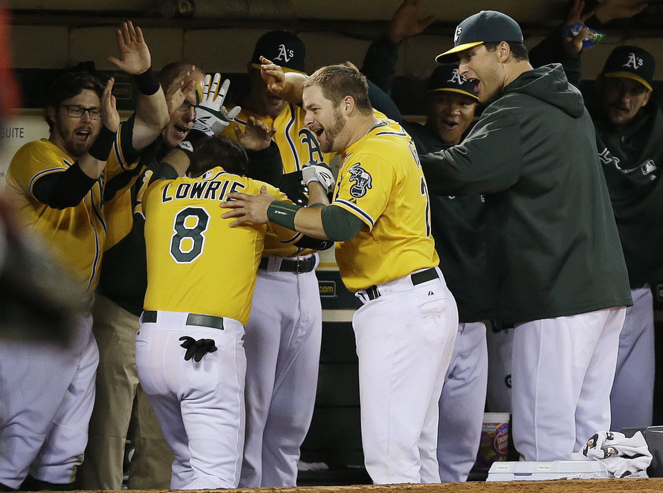 Oakland Athletics\' Jed Lowrie (8) celebrates with teammates in the dugout after hitting a three-run home run against the Minnesota Twins during the sixth inning of a baseball game on Thursday, Sept. 19, 2013, in Oakland, Calif. (AP Photo/Marcio Jose Sanchez)