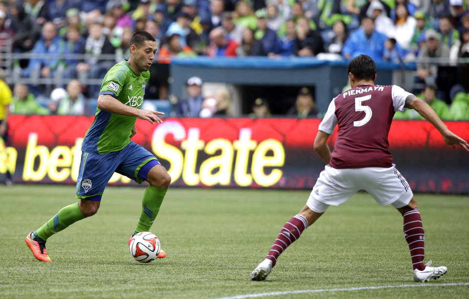 Photo - Seattle Sounders' Clint Dempsey, left, moves the ball around Colorado Rapids' Thomas Piermayr (5) in the second half of an MLS soccer match, Saturday, Aug. 30, 2014, in Seattle. The Sounders beat the Rapids, 1-0. (AP Photo/Ted S. Warren)