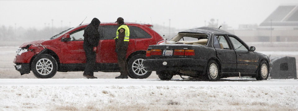 Photo - Authorities work the scene of an accident Thursday on the Kilpatrick Turnpike at MacArthur Boulevard in Oklahoma City. Photo by Bryan Terry, The Oklahoman