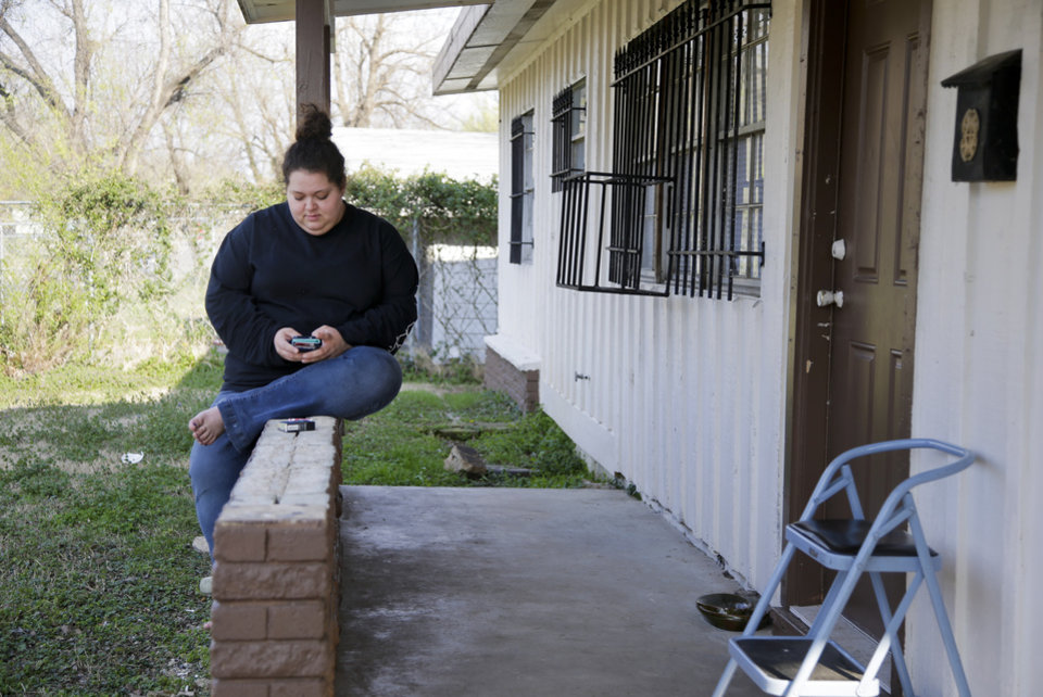 Photo -  Desha Bailey texts as she sits on her front patio in Tulsa. [Photo by Jessie Wardarski, Tulsa World]