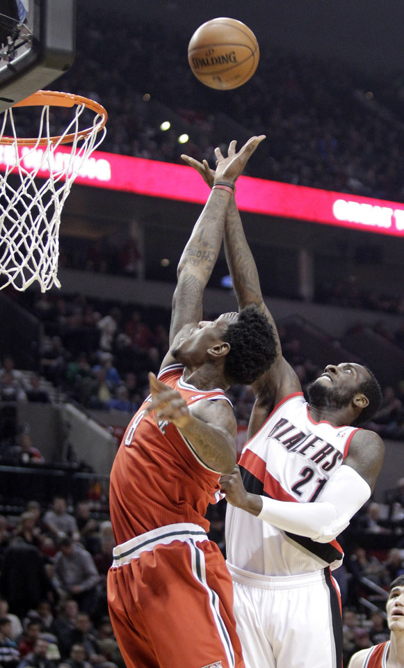 Portland Trail Blazers center J.J. Hickson, right, and Milwaukee Bucks center Larry Sanders reach for a rebound during the first quarter of an NBA basketball game in Portland, Ore., Saturday, Jan. 19, 2013. (AP Photo/Don Ryan)