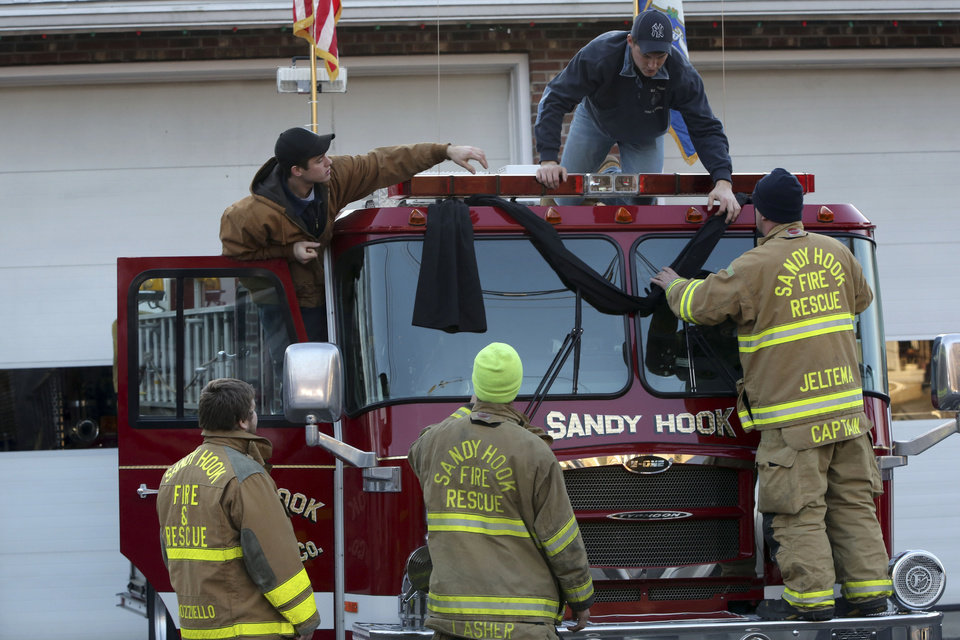 Photo - Sandy Hook firefighters hang bunting on their firetruck, Saturday, Dec. 15, 2012 in Sandy Hook village of Newtown, Conn.   The massacre of 26 children and adults at Sandy Hook Elementary school elicited horror and soul-searching around the world even as it raised more basic questions about why the gunman, 20-year-old Adam Lanza, would have been driven to such a crime and how he chose his victims.  (AP Photo/Mary Altaffer)