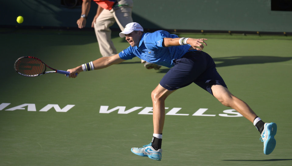 Photo - John Isner reaches to return a shot to Ernests Gulbis, of Latvia, during their quarterfinal match at the BNP Paribas Open tennis tournament, Friday, March 14, 2014, in Indian Wells, Calif. (AP Photo/Mark J. Terrill)
