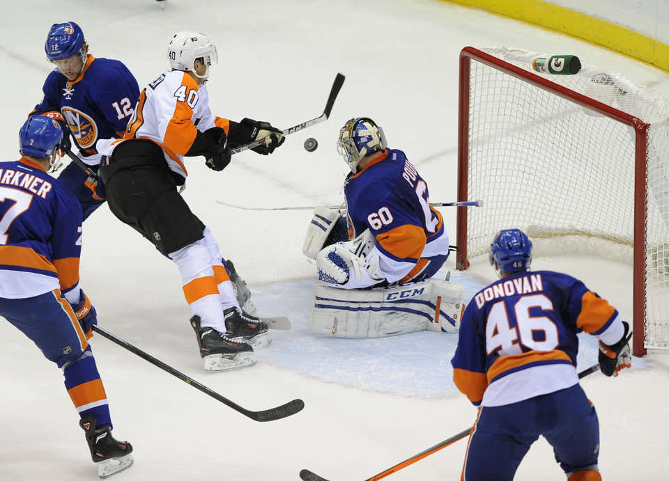 Photo - Philadelphia Flyers' Vincent Lecavalier (40) shoots the puck past New York Islanders' Josh Bailey (12) and goalie Kevin Poulin (60) to score his second goal in the first period of an NHL hockey game at the Nassau Coliseum on Saturday, Oct. 26, 2013, in Uniondale, N.Y. (AP Photo/Kathy Kmonicek)
