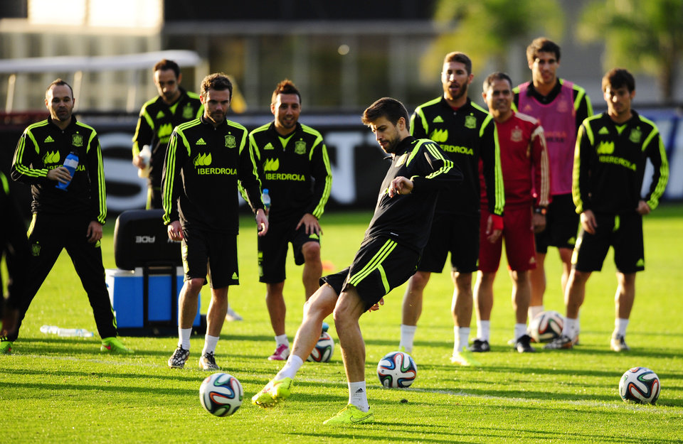 Photo - Spain's Gerard Pique kicks the ball during a training session at the Atletico Paranaense training center in Curitiba, Brazil, Sunday, June 15, 2014. Spain will play in group B of the Brazil 2014 World Cup. (AP Photo/Manu Fernandez)