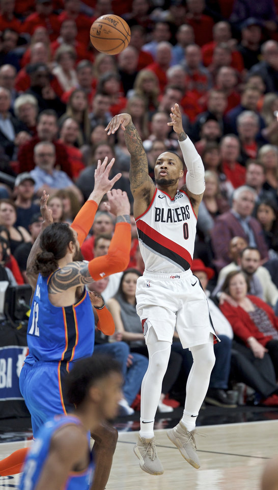 Photo - Portland Trail Blazers guard Damian Lillard, right, shoots over Oklahoma City Thunder center Steven Adams during the second half of Game 2 of an NBA basketball first-round playoff series Tuesday, April 16, 2019, in Portland, Ore. (AP Photo/Craig Mitchelldyer)
