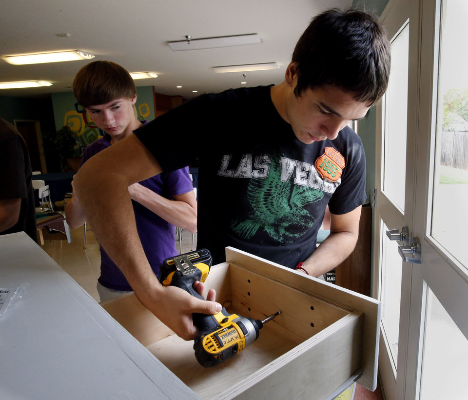 Moore Norman Technology Center student Jesse Stevens prepares to install a custom-built dresser and bookshelve unit at Bridges. PHOTO BY STEVE SISNEY, THE OKLAHOMAN <strong>STEVE SISNEY</strong>