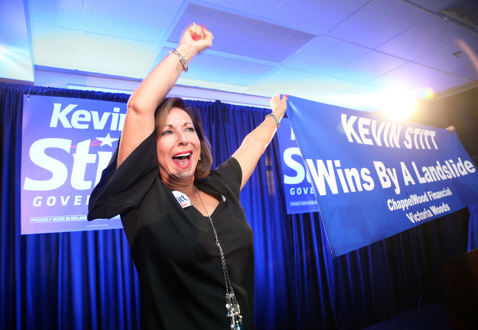 Photo - Victoria Woods raises a banner celebrating  gubernatorial candidate Kevin Stitt's victory over Mick Cornett during a watch party in Jenks, Okla., on Tuesday, August 28, 2018. MATT BARNARD/Tulsa World