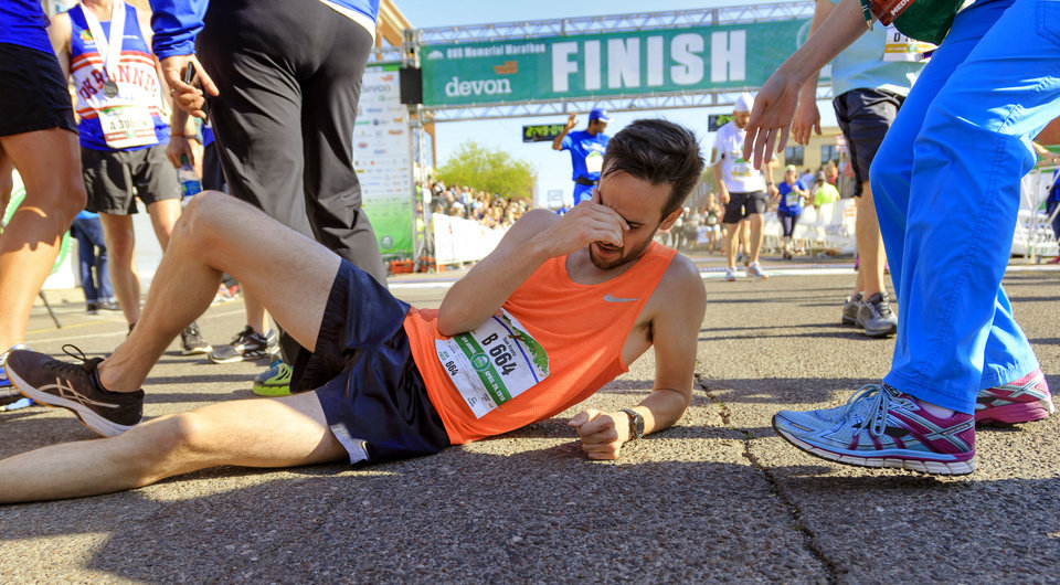 Photo - Tom Frantz takes a moment to rest as he lies on the ground after finishing the marathon during the Oklahoma City Marathon in Oklahoma City, Okla. on Sunday, April 29, 2018.  . Photo by Chris Landsberger, The Oklahoman