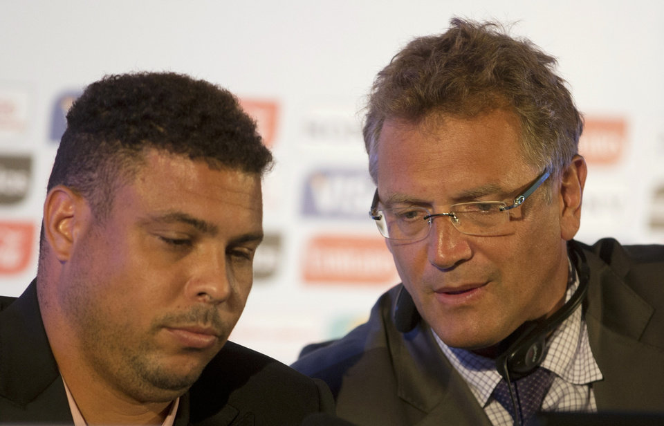 Photo - FIFA's secretary general Jerome Valcke, right, and former soccer player Ronaldo attend a press conference in Rio de Janeiro, Brazil, Thursday, Aug. 22, 2013. FIFA's secretary general has floated an idea for a possible change to the World Cup bidding process in response to a spate of challenges in organizing next year's tournament in Brazil, which he says has