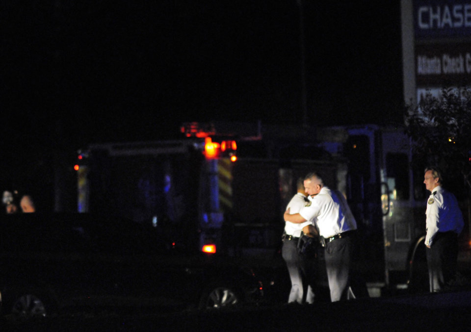 Law enforcement personnel embrace early Sunday, Nov. 4, 2012, as others investigate the scene of an Atlanta Police Department helicopter crash that killed two officers aboard the aircraft when it crashed near a shopping center late Saturday, Nov. 3, 2012. (AP Photo/David Tulis)