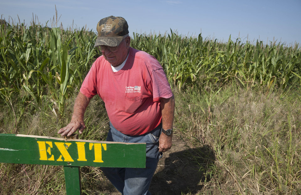 Photo -   In this photo taken Tuesday, Oct. 2, 2012, Bob Schaefers checks a sign at his corn maze near Mayflower, Ark. Devastating spring freezes and this year's historic drought have taken some of the charm out of rustic fall destinations, leaving some corn mazes too short for labyrinth duty, orchards virtually devoid of U-pick apples and fall colors muted. (AP Photo/Danny Johnston)