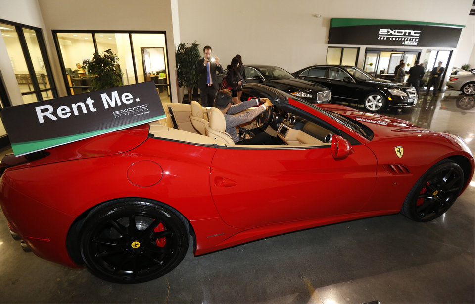 Photo - In this Wednesday, March, 26, 2014 photo, customer Luis Montelongo, from Monterrey, Mexico has his photo taken on a 2014 Ferrari California displayed for rent at the Enterprise Exotic Car Collection showroom near Los Angeles International Airport. (AP Photo/Damian Dovarganes)
