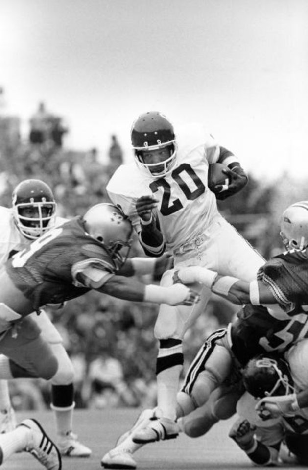 Photo -  Oklahoma back Billy Sims crashes through the Ohio State defense for a first down of a 1977 game in Columbus. [AP PHOTO]