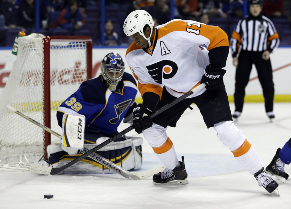 Photo - Philadelphia Flyers' Wayne Simmonds (17) controls the puck as St. Louis Blues goalie Ryan Miller watches during the first period of an NHL hockey game Tuesday, April 1, 2014, in St. Louis. (AP Photo/Jeff Roberson)