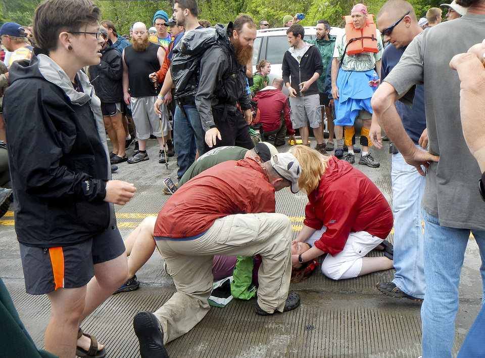 Photo - People attend to a victim who was hit by a car during the Hikers Parade at the Trail Days festival in Damascus, Va., Saturday, May 18, 2013. Witnesses said the car drove into a crowd at the parade and hurt several people, but the nature of their injuries wasn't immediately known. (AP Photo/Republican-American, Bill O'Brien)