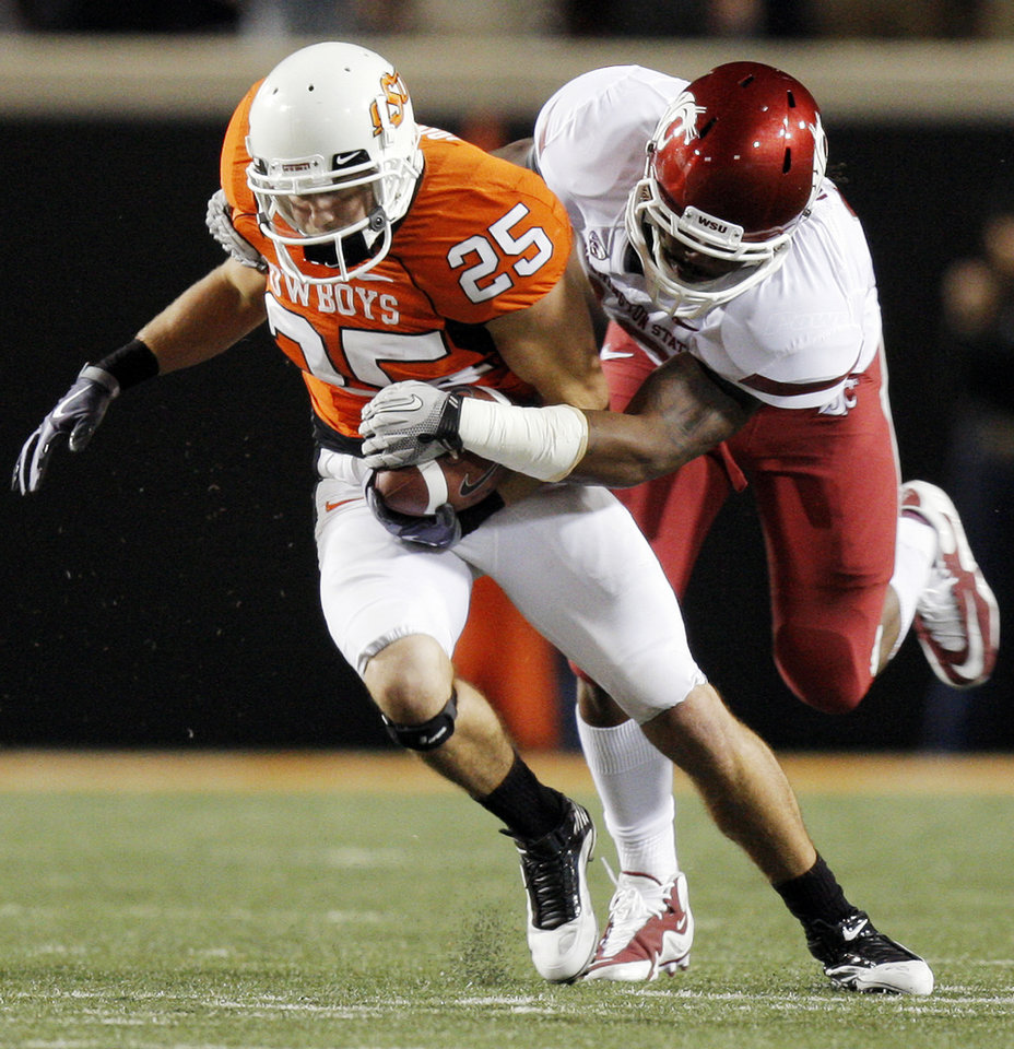 Photo - OSU's Josh Cooper is tackled by C.J. Mizell of WSU after a catch during the college football game between the Washington State Cougars (WSU) and the Oklahoma State Cowboys (OSU) at Boone Pickens Stadium in Stillwater, Okla., Saturday, September 4, 2010. OSU won, 65-17. Photo by Nate Billings, The Oklahoman
