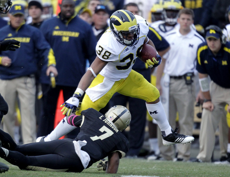 Michigan running back Thomas Rawls (38) tries to get over Purdue safety E.J. Johnson as he picks up 19 yards during the second half of an NCAA college football game in West Lafayette, Ind., Saturday, Oct. 6, 2012. Michigan defeated Purdue 44-13. (AP Photo/Michael Conroy)