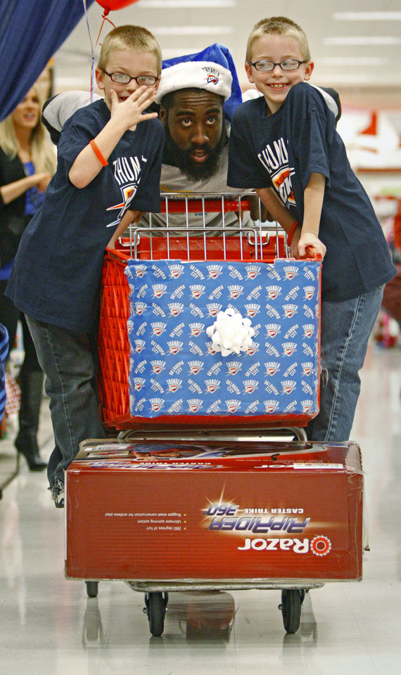 Photo - James Harden with the Oklahoma City Thunder shops with Jeremy Underhill, 7, left, and Jason Underhill, 7, during a shopping spree with the Sunbeam Family Services Grandparents Raising Grandkids program and the Thunder at a Target store in Oklahoma City, Thursday, December 16, 2010.  Photo by Bryan Terry, The Oklahoman