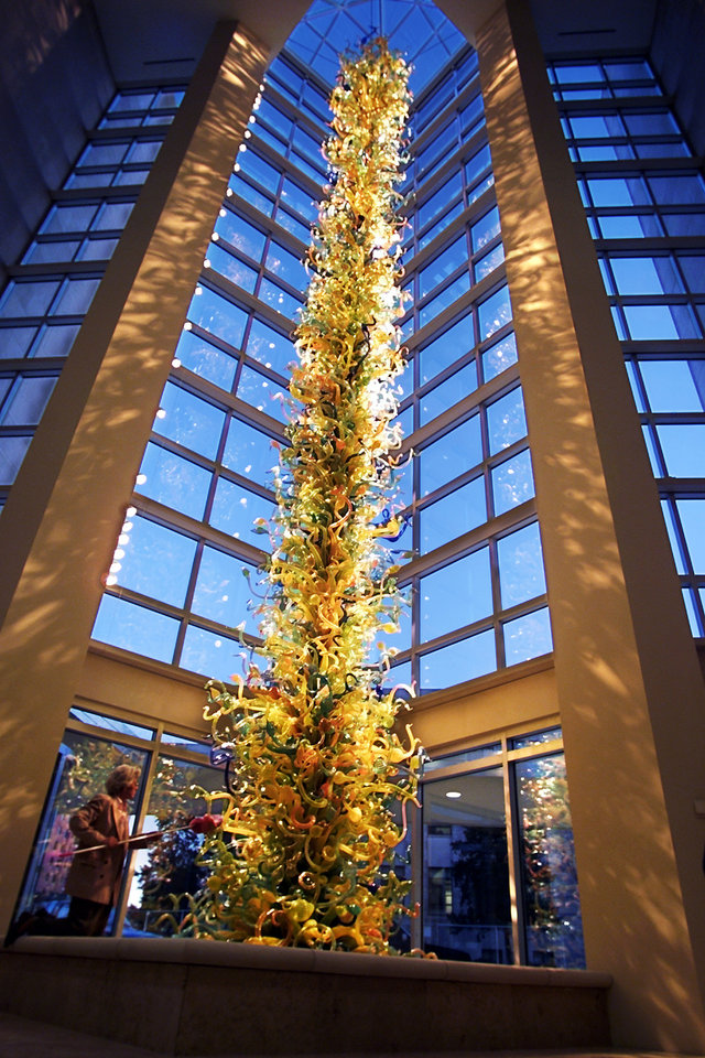 Photo - Executive Director of the Oklahoma City Art Museum Carolyn Hill dusts off the 55 foot towering blown glass sculpture by Seattle Artist Dale Chihuly.   Staff photo by Steve Sisney