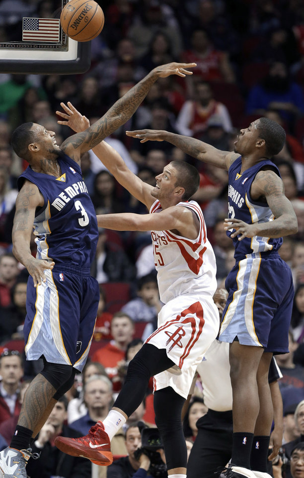 Photo - Houston Rockets' Chandler Parsons (25) is double-teamed by Memphis Grizzlies' James Johnson (3) and Ed Davis during the first half of an NBA basketball game Friday, Jan. 24, 2014, in Houston. (AP Photo/Pat Sullivan)